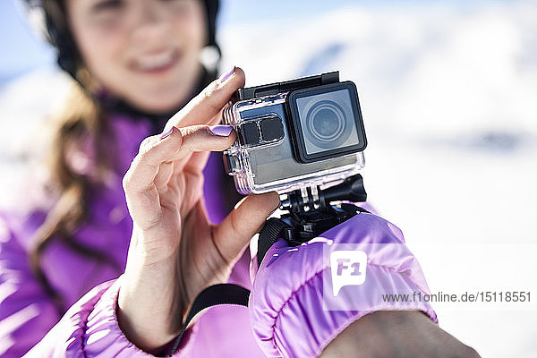 Close-up of woman in ski clothes filming with an action camera