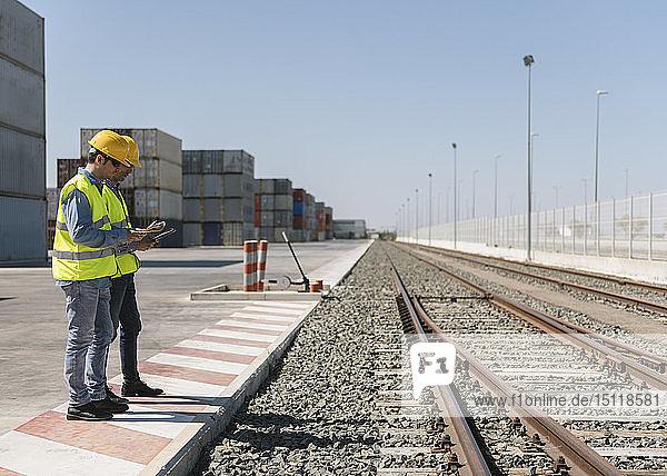 Arbeiter vor Frachtcontainern in der Nähe von Eisenbahnschienen auf einem Industriegelände