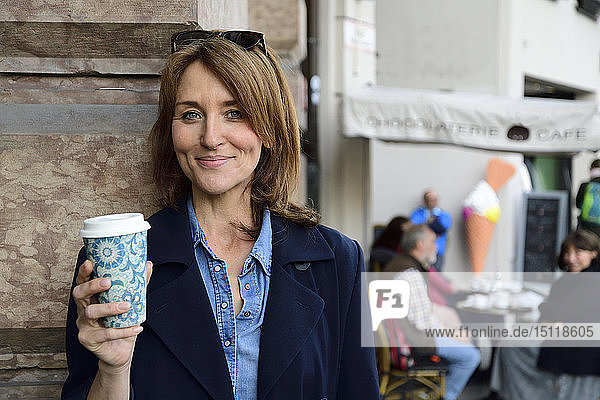 Portrait of smiling mature woman with reusable bamboo cup in the city