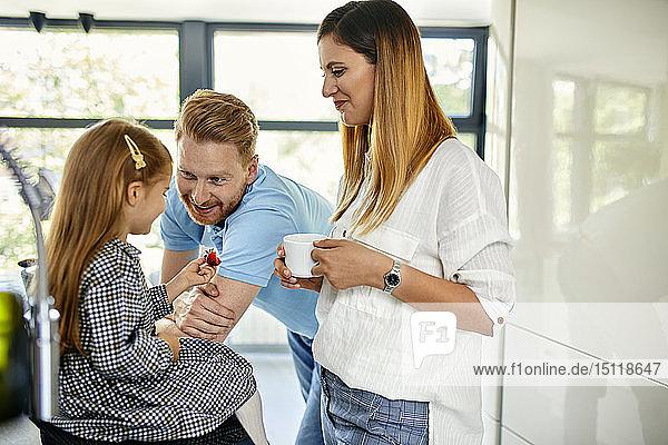 Glückliche Familie isst frische Erdbeeren in moderner Küche