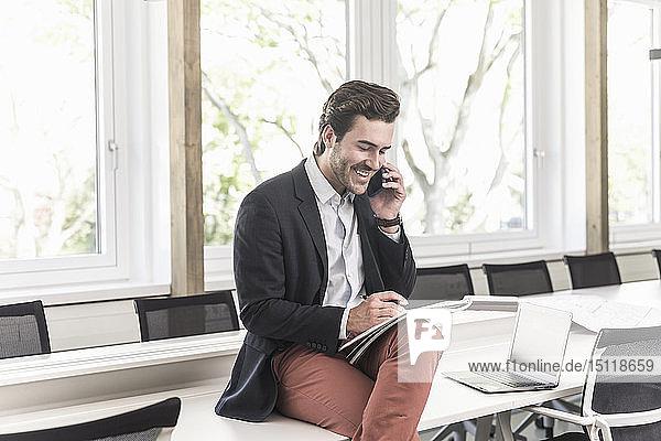 Junger Geschäftsmann sitzt im Sitzungssaal  spricht am Telefon