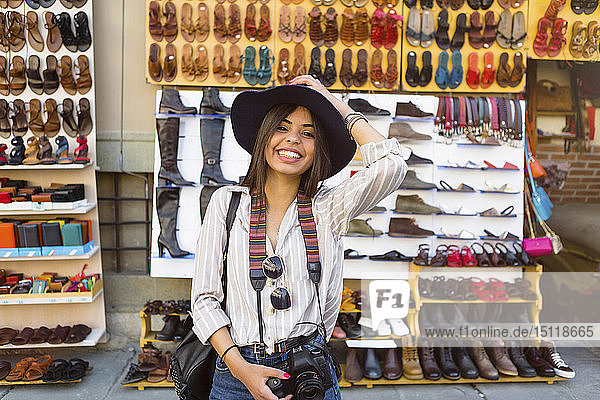 Italy  Florence  portrait of happy young tourist with camera and backpack on street market