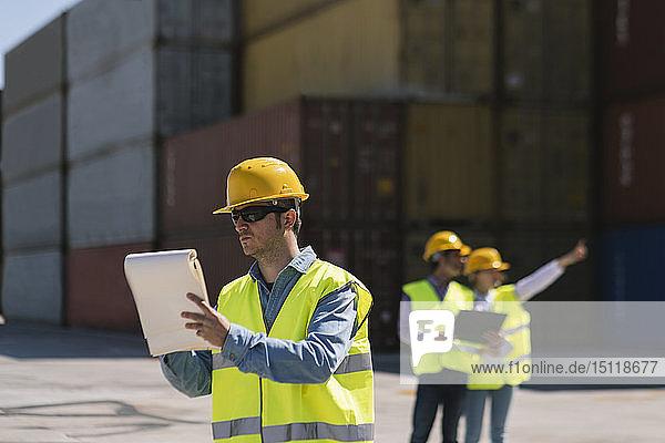 Arbeiter vor Frachtcontainern auf einem Industriegelände