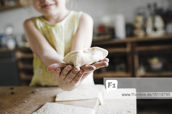 Girl's hands holding homemade stuffed pastry  close-up