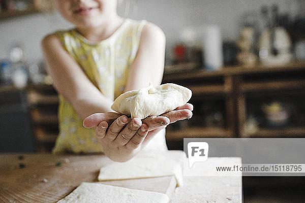 Mädchenhände mit hausgemachtem gefüllten Gebäck  Nahaufnahme