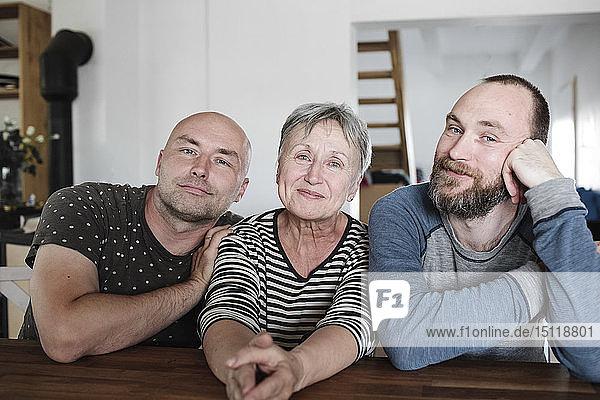 Porträt von lächelnden erwachsenen Söhnen mit älterer Mutter zu Hause