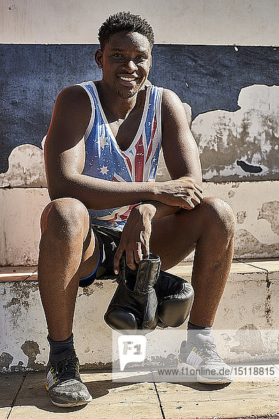 Portrait of smiling boxer with his boxing gloves sitting outdoors after training