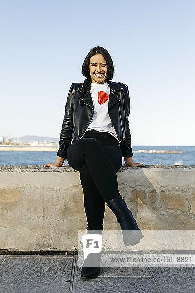 Junge Frau sitzt auf einer Mauer  im Hintergrund das Meer