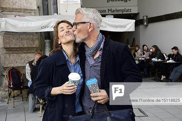 Erwachsenes Paar mit wiederverwendbaren Bambusbechern küsst sich in der Stadt