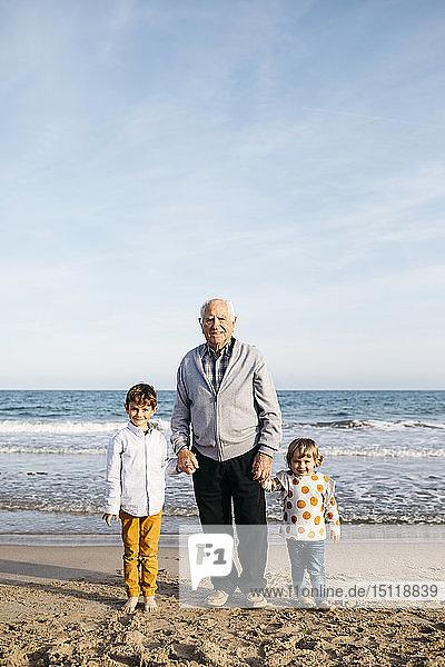 Porträt eines glücklichen Grossvaters  der mit seinen Enkelkindern Hand in Hand am Strand steht