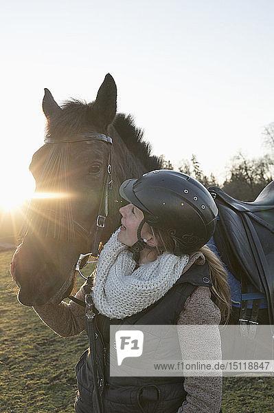 Junge Frau mit Pferd im Gegenlicht