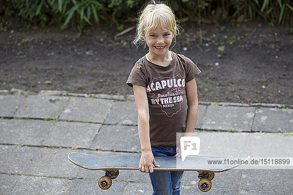 Portrait of smiling girl with skateboard