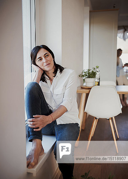 Mature woman sitting on windowsill in the kitchen  daydreaming