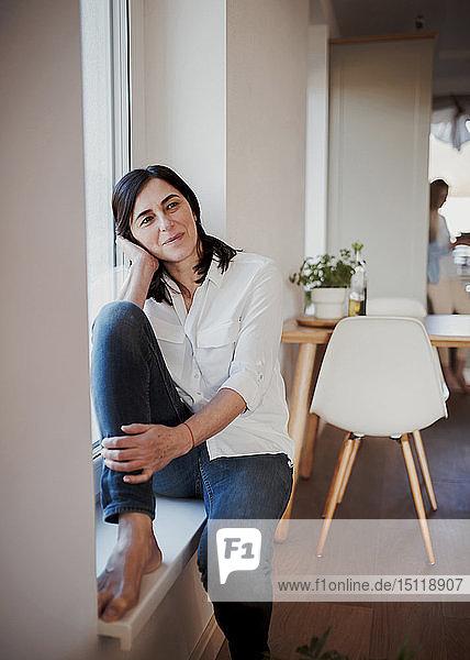 Reife Frau sitzt auf der Fensterbank in der Küche und träumt