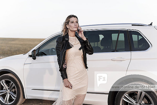 Blond woman using smartphone  white car in the background