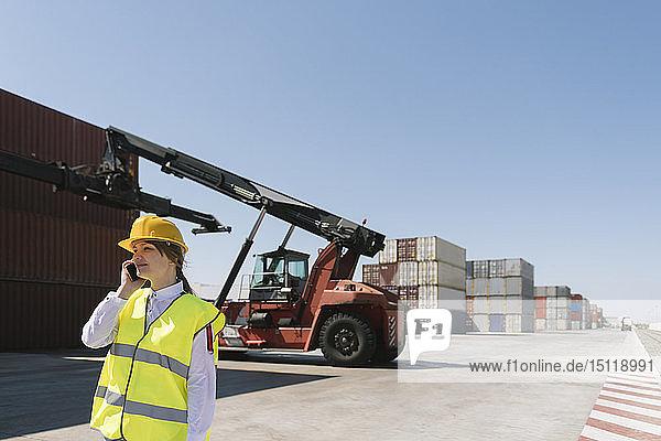 Arbeitnehmerin am Telefon vor einem Kran mit Frachtcontainer auf einem Industriegelände
