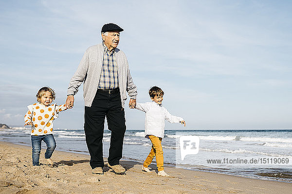 Grandfather strolling with his grandchildren hand in hand on the beach