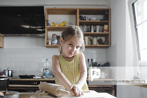 Portrait of smiling little girl kneading dough in the kitchen