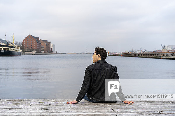 Dänemark  Kopenhagen  Rückansicht eines am Wasser sitzenden jungen Mannes