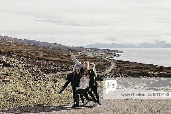Großbritannien,  Schottland,  Highland,  glückliche Freundinnen auf einer Straße an der Küste