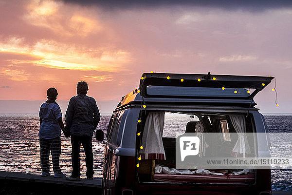Älteres Ehepaar reist in einem Oldtimer-Van und betrachtet den Sonnenuntergang am Meer