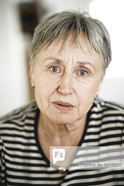 Porträt einer älteren Frau mit kurzen Haaren  die respektabel in die Kamera schaut