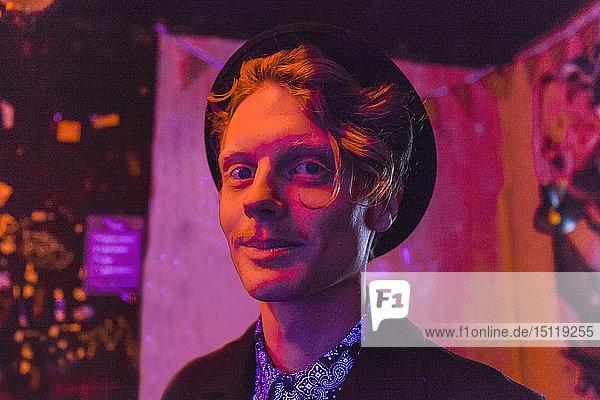 Junger Mann mit Hut bei psychedelischer Party  Effekte einer Lichtmaschine an einer Wand