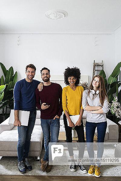 Porträt von vier glücklichen Freunden  die nebeneinander im Wohnzimmer stehen