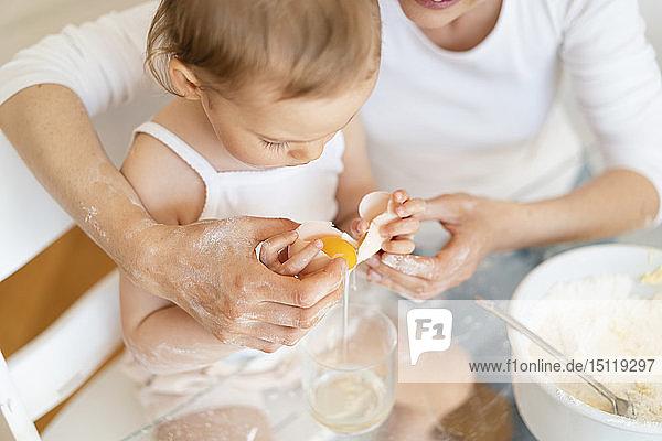 Mutter und kleine Tochter backen zu Hause in der Küche gemeinsam einen Kuchen und schlagen ein Ei auf