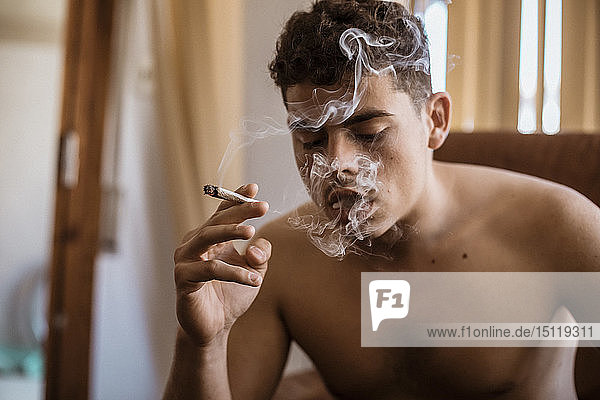 Barfüssiger Mann raucht einen Joint Marihuana