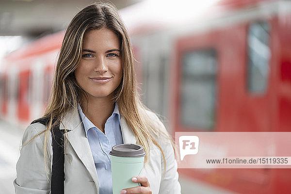 Junge Geschäftsfrau mit Kaffee zum Mitnehmen  auf dem Bahnhof stehend