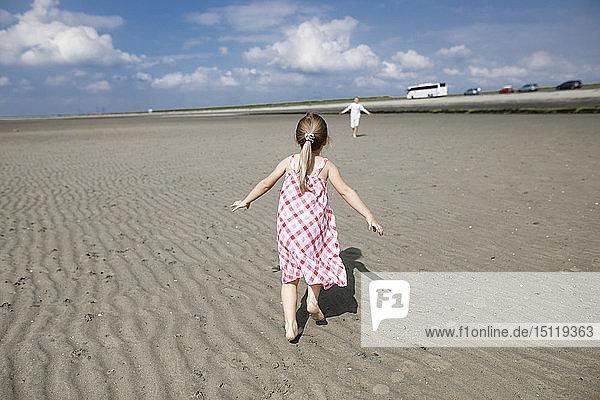 Rückenansicht eines kleinen Mädchens  das am Strand läuft  Bergen op Zoom  Niederlande