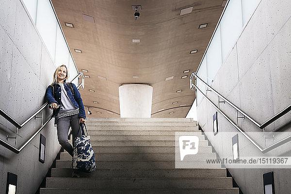 Lächelnde Frau auf der Treppe am Bahnhof