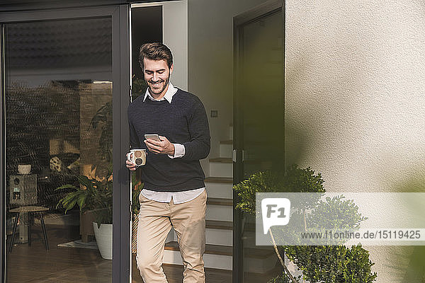 Young man leaning in door of his house  holding cup of coffee  using smartphone