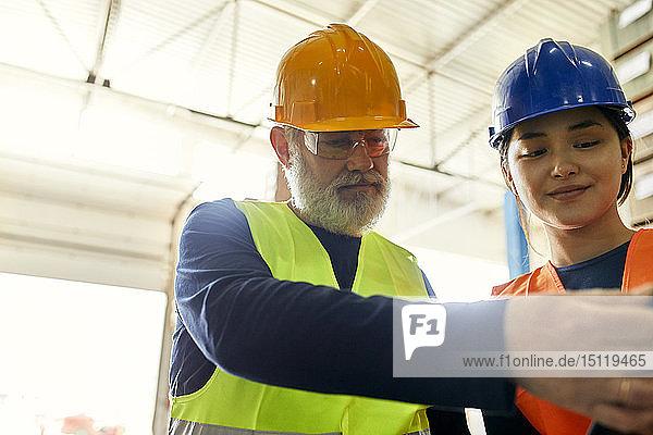 Männliche und weibliche Arbeitnehmer arbeiten in der Fabrik zusammen