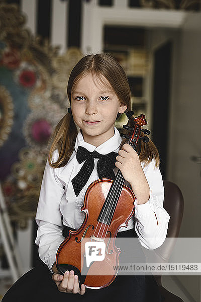 Portrait of a smiling girl with a violin at home