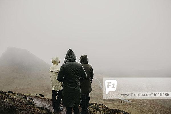 UK  Schottland  Isle of Skye  Quiraing Viewpoint  Rückansicht von drei Frauen in nebliger Landschaft