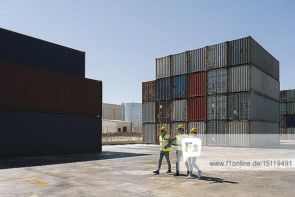 Arbeiter gehen gemeinsam in der Nähe eines Stapels von Frachtcontainern auf einem Industriegelände