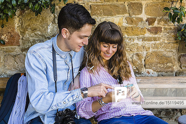 Young couple on a city break  sitting on a bench  using smartphone