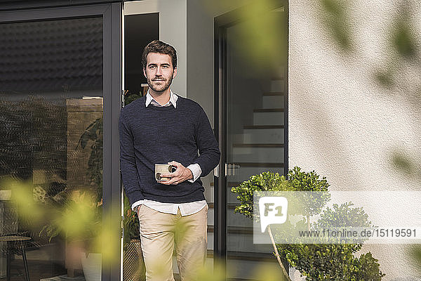 Young man leaning in door of his house  with a cup of coffee
