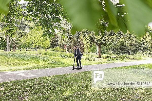 Geschäftsmann mit E-Scooter im Stadtpark