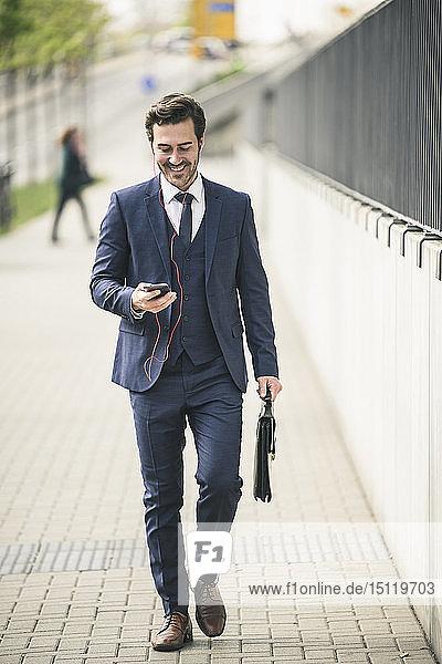Geschäftsmann  der mit Handy und Kopfhörern durch die Stadt läuft
