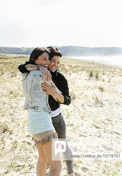 Zwei glückliche Freundinnen umarmen sich am Strand