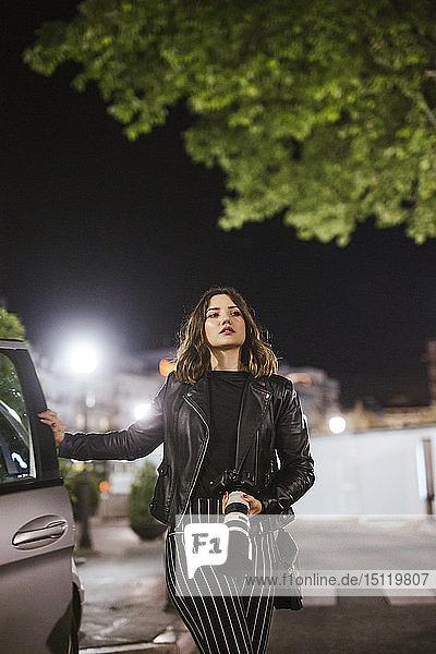 Young woman with camera at a car at night