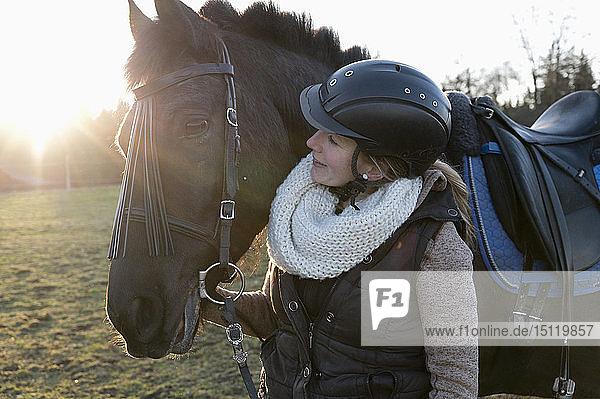 Lächelnde Frau mit Pferd im Gegenlicht