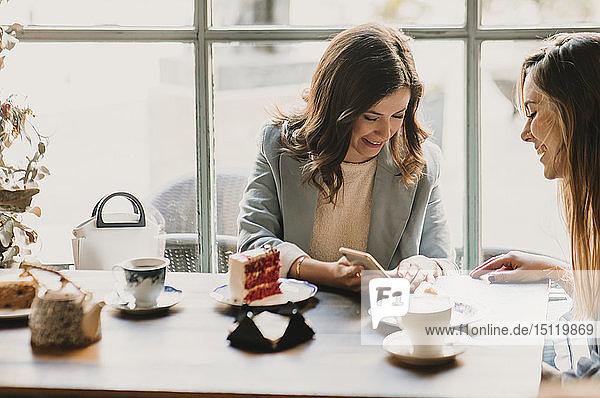 Junge Frau zeigt einem Freund in einem Café ihr Handy