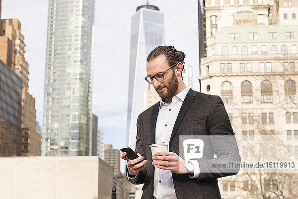 Bärtiger junger Geschäftsmann mit Kaffee zum Handybesuch  New York City  USA