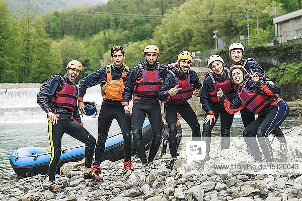 Gruppe spielerischer Freunde bei einem Rafting-Kurs  die am Boot posieren