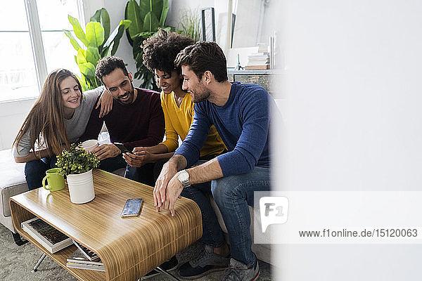 Vier glückliche Freunde sitzen auf der Couch und telefonieren