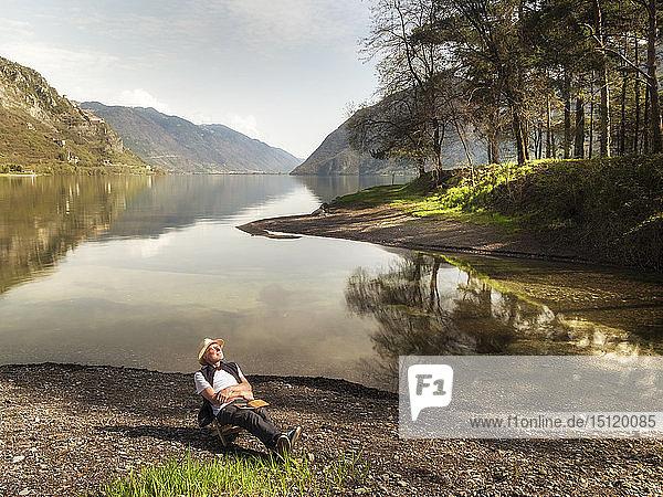 Italy  Lombardy  senior man relaxing at Lake Idro